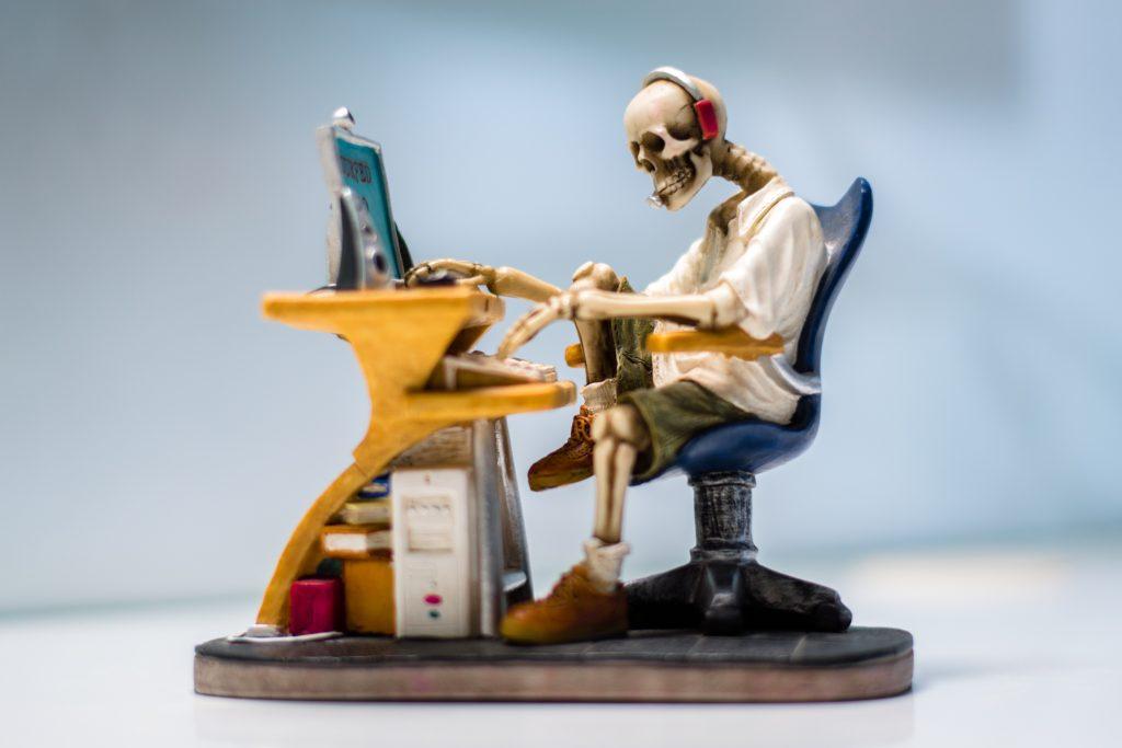 skeleton sitting at computer