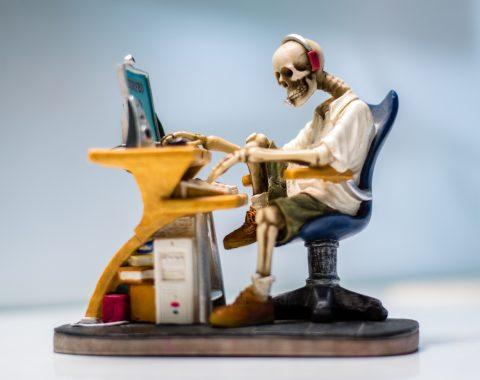 skeleton sitting at computer thumb